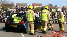 Fire fighters free trapped motorists in a road crash reconstruction