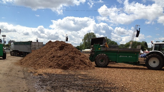 Tractors move wood chippings around the site.