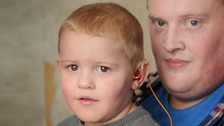 Two-year-old Ethan, pictured with dad Kyle, wears two hearing aids.