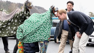 The Duke of Cambridge is greeted by Lion Dancers.