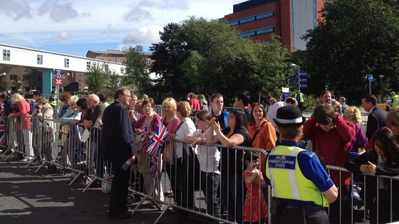 Crowds are ushered into place ahead of the Queen&#x27;s arrival at the QE Hospital