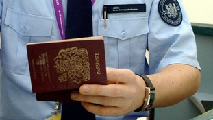 A member of the Border Force checks a passport.