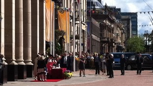 Queen signing the visitors book outside the Council House