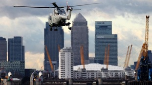 A military helicopter hovers in front of Canary Wharf.