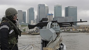 A member of the Royal Navy mans a gun at the bow of HMS Ocean.