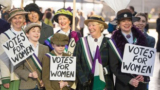 Participants dressed in suffragette period costume take part in CARE International's Walk in Her Shoes march in central London