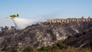 A plane assists in putting out a forest fire at the hills in Valparaiso city