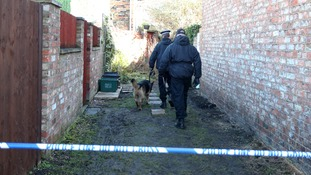 Police pictured searching an alleyway near Claudia Lawrence's home in February.