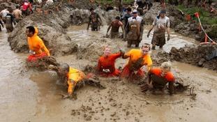 Team of people wade through mud