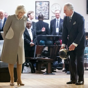 Camilla laughs as Prince Charles attempts to strike it lucky on a visit to the Armed Forces Retirement Home in Washington