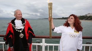 Bournemouth Mayor Philip Stanley-Watts (left) looking on Mariam Kazem-Malaki carries the Olympic Flame