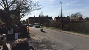 The cortege makes its way into the village as hundreds watch