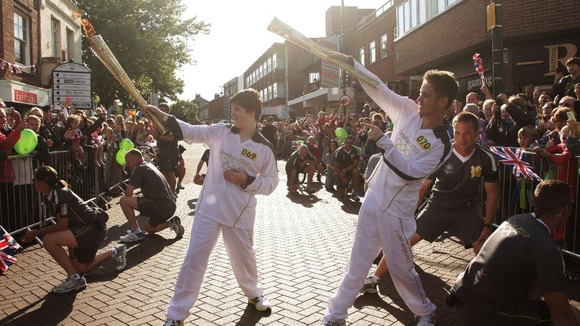 Torchbearers Samuel Smith and Christopher Smith imitating Usain Bolt's celebration whilst carrying the Olympic Flame