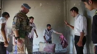A resident in Tremseh shows an UN observer blood stained items in a house