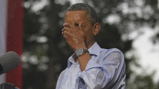 U.S. President Barack Obama wipes rain off his face during heavy rainfall at a campaign rally in Glen Allen