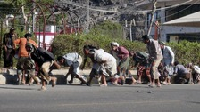 People seek shelter during a gunfire at an army base in Yemen's southern port city of Adem yesterday