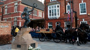 King Richard III's coffin arrives outside Leicester Cathedral, next to a statue of Richard III.