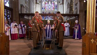 The soldiers lowered the coffin into the ground