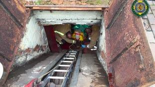 Paramedics treat an elderly man who fell into a pub cellar yesterday