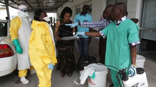 A health worker sprays a colleague with disinfectant.