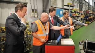 David Cameron and Nick Clegg with engineers Garry Matthews (left) and Michael Bailey at the Soho Depot in Smethwick.