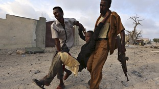 Residents evacuate an injured boy after Islamist group al Shabaab attacked the Maka Al-Mukarama hotel in Mogadishu