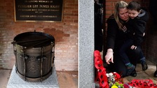 Rigby's widow Rebecca touches the memorial at the service.