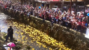 Crowds line the banks of the river at Heden Bridge to watch the event