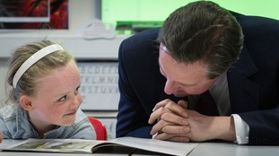 The Prime Minister reads a children's book to pupil Lucy Howarth