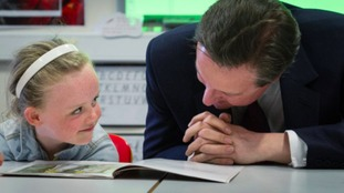 David Cameron reading a book to a child