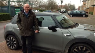 Adrian Masters stands next to the Mini Cooper which he's driven across Wales for the series