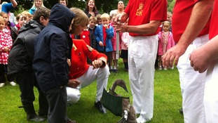 A cygnet is weighed by school children