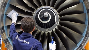 A worker services at Rolls Royce jet engine.