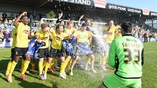 Burton Albion players celebrate being promoted to League One.