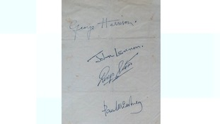 A piece of paper signed by all four Beatles.