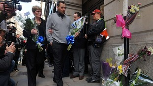 Ian Tomlinson's widow Julia Tomlinson (left) and stepson Paul King, arrive with flowers at a memorial in London.