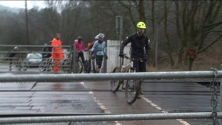 Cyclists being guided over the level crossing at Moors Gorse by a Network Rail worker
