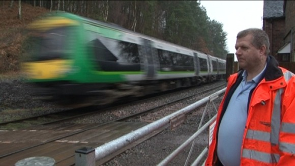 Network Rail worker closes barrier as London Midland train passes
