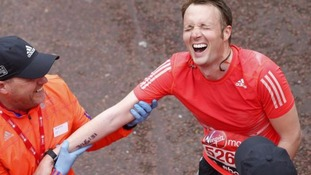 A man is helped after finishing the Virgin Money London Marathon.