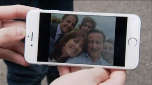 Cameron takes a selfie with first time voter and his family.