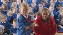 Shelby Watson presents Lucy Glendinning with her medal