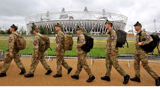 Group of soldiers from the Royal Regiment of Scotland march in front of the Olympic stadium