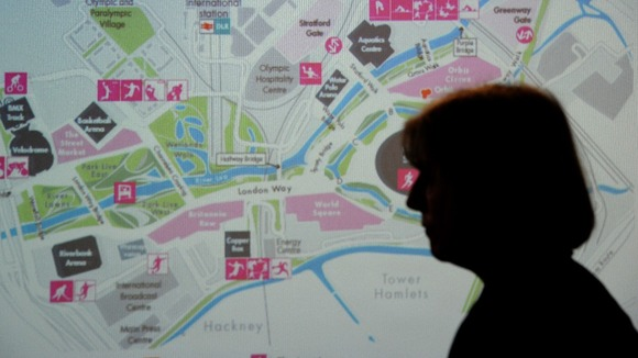 Theresa May stands in front of a map of the Olympic Park
