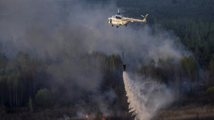 A firefighting helicopter drops water on the blaze