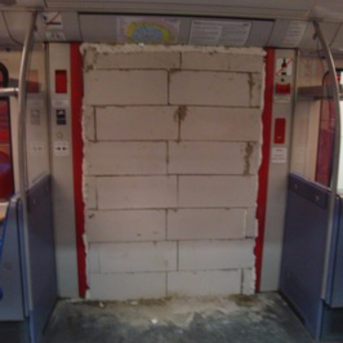The wall was built using breeze blocks and expanding foam as an adhesive & Subway train evacuated after vandals brick up doorway - ITV News