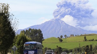 Vehicles travel along a road as smoke and ash rise from the Calbuco volcano