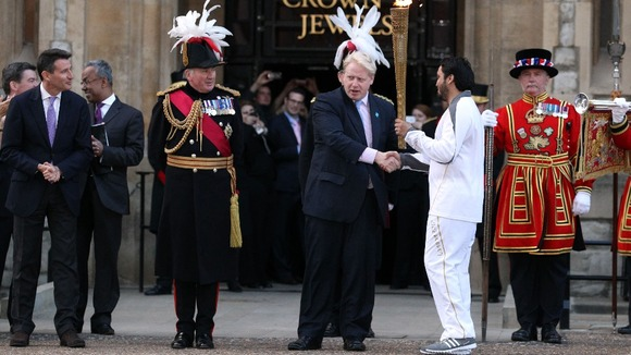 Abul Kasam shaking hands with Mayor of London Boris Johnson as he holds the Olympic flame