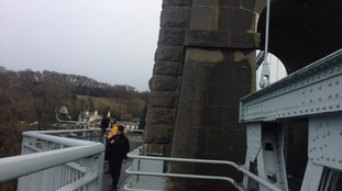 Pedestrians cross the Menai Bridge in Anglesey, North Wales