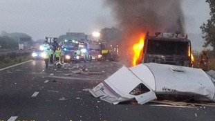 The lorry on fire after the collision between the lorry and a car towing the caravan on the M6