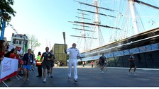 Robin Knox-Johnston, the first person to sail non-stop around the world, runs the torch around Cutty Sark.